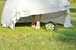 Bride's. Beautiful bride's feet over green grass with flower bouquet Royalty Free Stock Photography