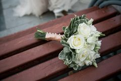 The bride`s beautifully decorated bouquet of white roses and green leaves lies on a brown wooden bench. Wedding theme royalty free stock image