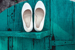 Bride`s biege shoes on heel on a wooden board tiffany colour Royalty Free Stock Images