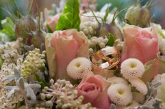 Brides boquet with rings. Wedding rings with roses and other flowers Stock Photos