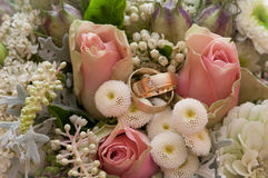 Brides boquet with rings. Wedding rings with roses and other flowers Stock Image