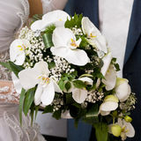 Bride's bouquet. Bride hold the bouquet from orchids and stand near the groom Stock Photos