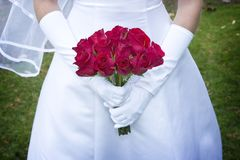 Bride's Bouquet. A simple bouquet of red roses is held with gloved hands by a lovely bride Royalty Free Stock Photo