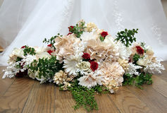 A bride's bouquet. And the foot of her wedding dress stock photography