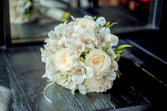 The bride`s bouquet. Bridal bouquet. The bride`s bouquet. Beautiful bouquet of white, blue, pink flowers and greenery, decorated with long silk ribbon, lies on Royalty Free Stock Images