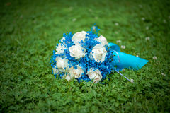 The bride`s bouquet. Bridal bouquet. The bride`s bouquet. Beautiful bouquet of white, blue, pink flowers and greenery, decorated with long silk ribbon, lies on Stock Images