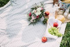 The bride`s bouquet and fruit lying on the picnic blanket stock photo