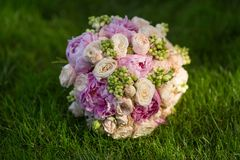 Bride's Bouquet on Green Grass. Still Life of Bride's Pink Orange and White Bouquet Stock Photos