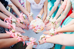 Bride's bouquet in her hands and friends. Bride's bouquet in her hands. Beautiful wedding bouquet in hands of a bride. Selective focus. Young bride holding the Stock Photos