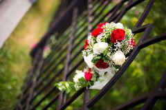 A bride`s bouquet is inserted into a fence