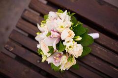 Bride s bouquet lies on a wooden bench, close-up top view