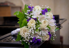 The bride`s bouquet lying on the piano. The bride`s bouquet with white roses and purple carnations lying on the piano closeup Stock Images