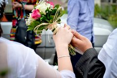 Bride`s bouquet outdoor. Bride`s bouquet in the hands of the bride and groom Stock Photo