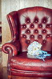 Bride's bouquet on a red armchair. Bride's bouquet on a red leather armchair Stock Image