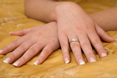 Bride's crossed hands showing a wedding ring. Bride's crossed hands showing a gold wedding ring on the light brown background Stock Photos