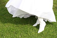 Bride's dress and boots. Bride wearing white gown and wearing white wedding boots.  View is of dress bottom and boots only.  Gown is blowing in breeze Royalty Free Stock Photography