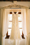 The bride`s dress hangs on the cornice Stock Photography