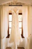 The bride`s dress hangs on the cornice Stock Photo