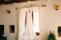 The bride`s dress hangs on the cornice Royalty Free Stock Photography