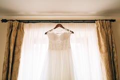 The bride`s dress hangs on the cornice Stock Photos