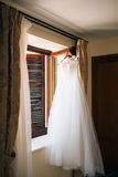 The bride`s dress hangs on the cornice Stock Photo