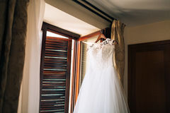 The bride`s dress hangs on the cornice Stock Photos