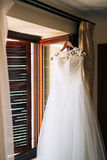 The bride`s dress hangs on the cornice Stock Images