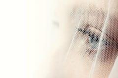 Bride's eye behind veil. Eye behind veil (selective focus on veil in front of eye Royalty Free Stock Photography