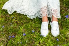 Bride`s feet in sneakers stock photos