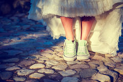 Bride's Feet in Sneakers. Hipster Wedding Concept. Bride's Legs in Sneakers. Modern Youth Hipster Style Wedding Concept. Toned and Filtered Photo with Copy Royalty Free Stock Images