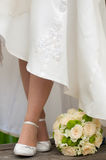 Bride's feet. In white shoes with flowers Royalty Free Stock Image