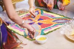 Bride`s friend helps coloring the traditional rice art Rangoli on the floor for indian wedding. Women helps coloring tradition colorful rice art or sand art Stock Photo