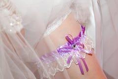 Bride's garter to the young slender leg. Stock Photos