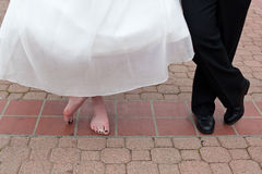 Bride's and Groom's feet. Bride in long white wedding dress barefoot and Groom standing on concrete tile floor Stock Photos
