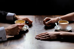 Bride's and groom's hands holding coffee cups. Bride's and groom's hands and coffee cups on the table Royalty Free Stock Photo