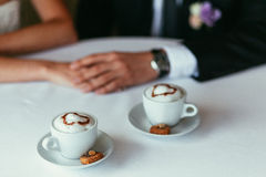 Bride's and groom's hands holding each other on a table with two Royalty Free Stock Photo
