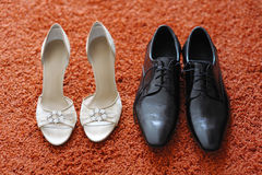 Bride's and groom's shoes. On red carpet Stock Photos