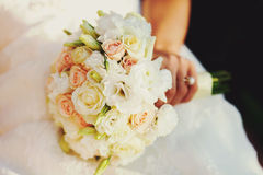 Bride's hand holds a wedding bouquet of white and creamy roses Stock Photo