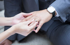 Bride's hand putting a wedding ring. On the groom's finger Stock Images