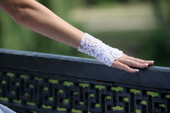 Bride's hand rests on the railing Stock Images