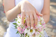 Bride's hand with a ring. On a bouquet closeup royalty free stock image