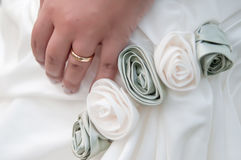 Bride's hand wearing wedding ring. Wedding, bride, ring and roses stock photo