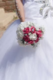 The bride's hand in a white dress with a bouquet of white and pink roses Royalty Free Stock Photos