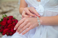 Bride's hands with the bracelet. Wedding bouquet in the backgrou Stock Photography