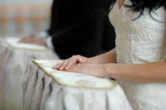 Bride's hands close-up during church ceremony. Bride's hands on the pillow close-up during wedding church ceremony Royalty Free Stock Photography