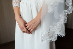 Bride`s hands crossed on dress. Bride`s hands crossed on white dress Royalty Free Stock Image