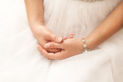 The bride's hands are crossed to a bracelet. On a stomach stock photography