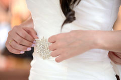 Bride's hands. Holding   belt with the broach Royalty Free Stock Photo