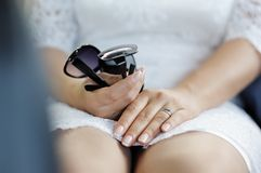Bride's hands holding sunglasses Stock Image