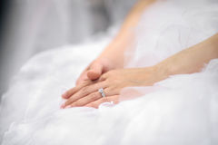 Bride's hands laying on wedding dress Stock Photo